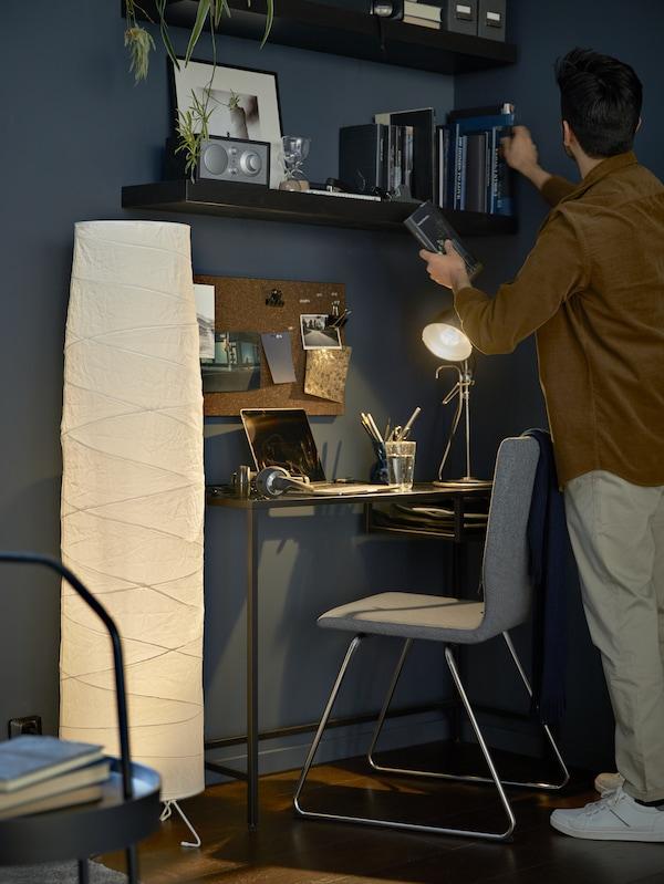 Un espace de travail compact formé d'une table à ordinateur portable noir-brun VITTSJÖ et une chaise VOLFGANG, avec des étagères murales LACK au-dessus.