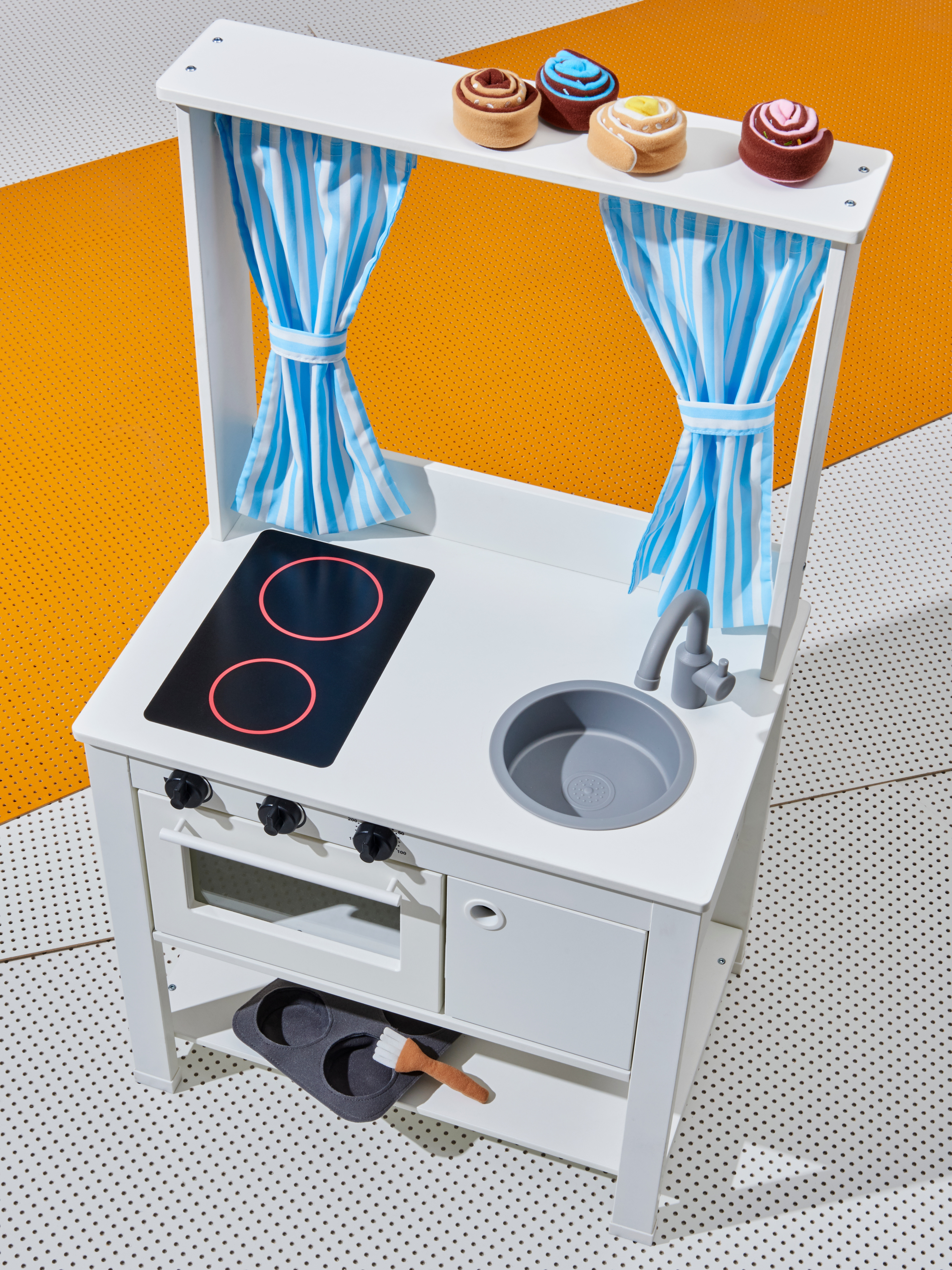 Front of children's white toy kitchen with induction cooktop and sink; striped curtains.