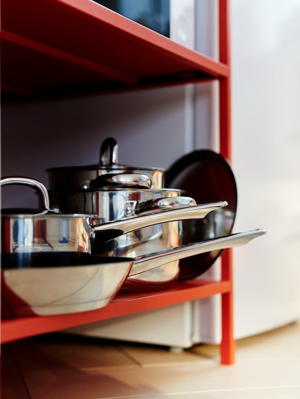 Pots and pans with lids stacked on the bottom shelf of an orange-red ENHET storage unit.