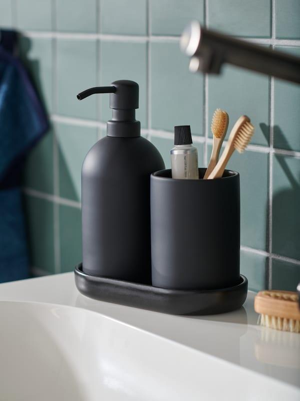 Et GANSJÖN badeværelsessæt af stentøj med tre dele står på hjørnet af en vask i et badeværelse med grønne fliser.