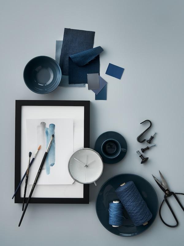 A kék árnyalaiban tündöklő különböző elemeket látunk szétszórtan: közöttük sötét türkiz FÄRGKLAR étkészletet, egy MALLHOPPA ébresztőórát, zsinórokat és textildarabokat.