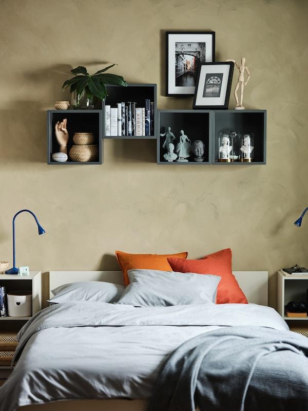 Fire mørkegrå vægmonterede reoler over en seng. På hylderne står der bøger, indrammet kunst, en dekorationshånd af træ og andre dekorative ting.