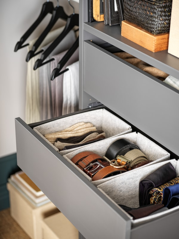 An open AURDAL drawer with belts organized in white KOMPLEMENT boxes.