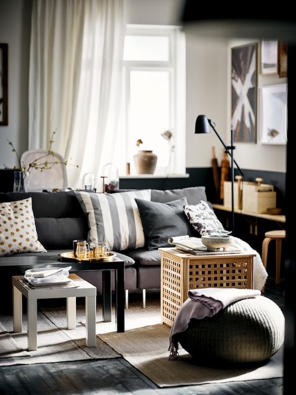 Ein sonnendurchflutetes Zimmer in Schwarzweiß mit schwarzen und weißen LACK Satztischen und einem dunkelgrauen SÖDERHAMN Sofa.