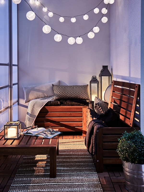 A balcony with wooden outdoor furniture with cushions, lamps, hanging lighting and a plant.
