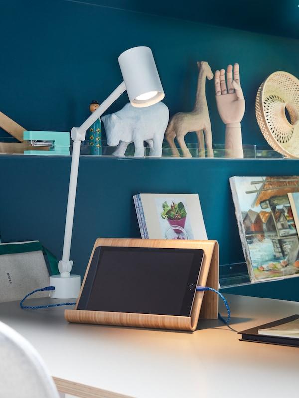 NYMÅNE-työvalolamppu valaisee jalustalla olevan tabletin ja lampun sisäänrakennetun USB-portin johto lataa tabletin.