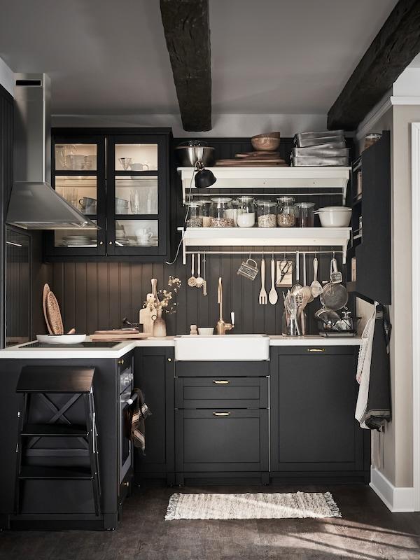 Sötét, hangulatos konyha, fekete szekrényekkel és fiókokkal, fekete fa borítású falakkal, fehér polcokkal és munkalapokkal.