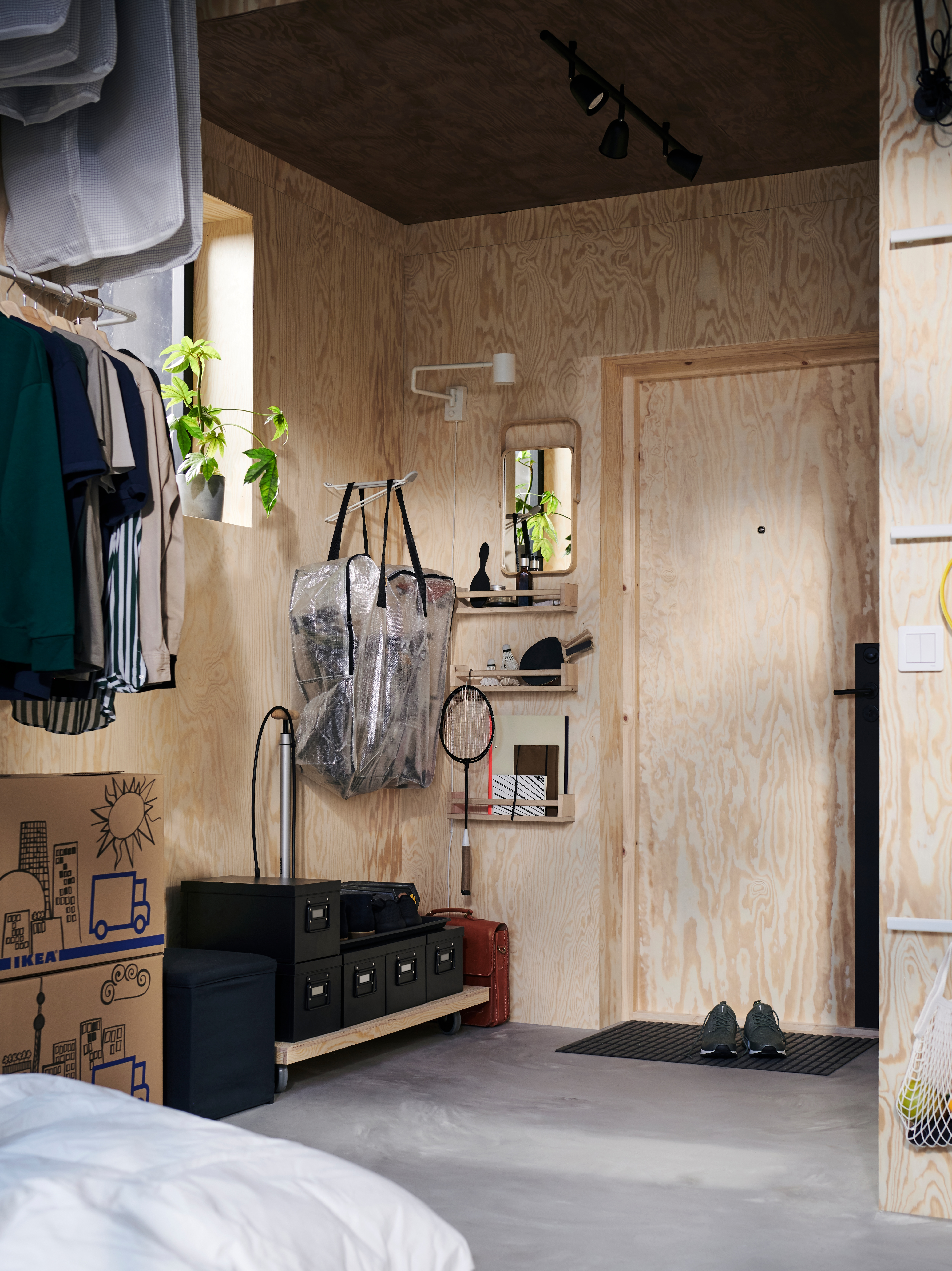 Hallway with storage bag, black storage boxes with lids, black footstool with storage space, wall lamp with swinging arm.