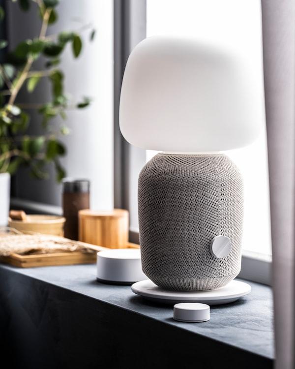 A white SYMFONISK WiFi speaker sitting on a large window sill