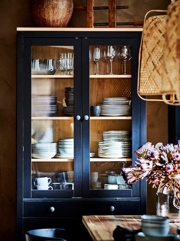 Una vetrina HEMNES con cassetti contenenti articoli per la tavola. Due lampade a sospensione KNIXHULT sono appese sopra il tavolo antistante.