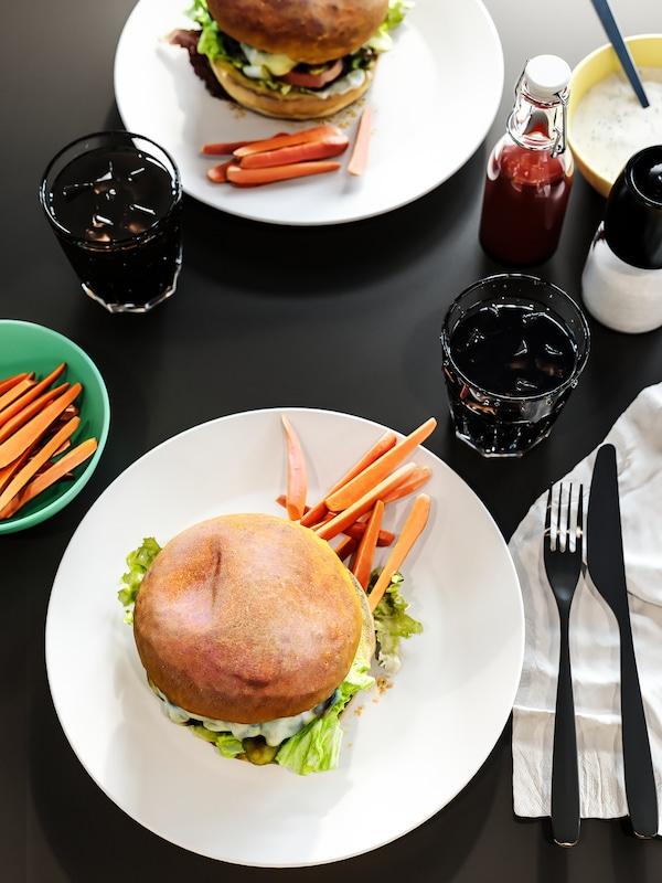 Tavolo color antracite con piatti di hamburger, bicchieri di cola, tovaglioli bianchi, condimenti e posate.