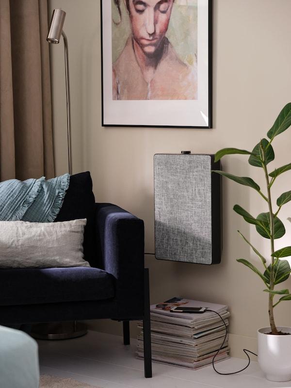 En lænestol, en gulv-/læselampe, et indrammet kunstværk, en luftrenser på væggen og en mobiltelefon, der ligger til opladning.
