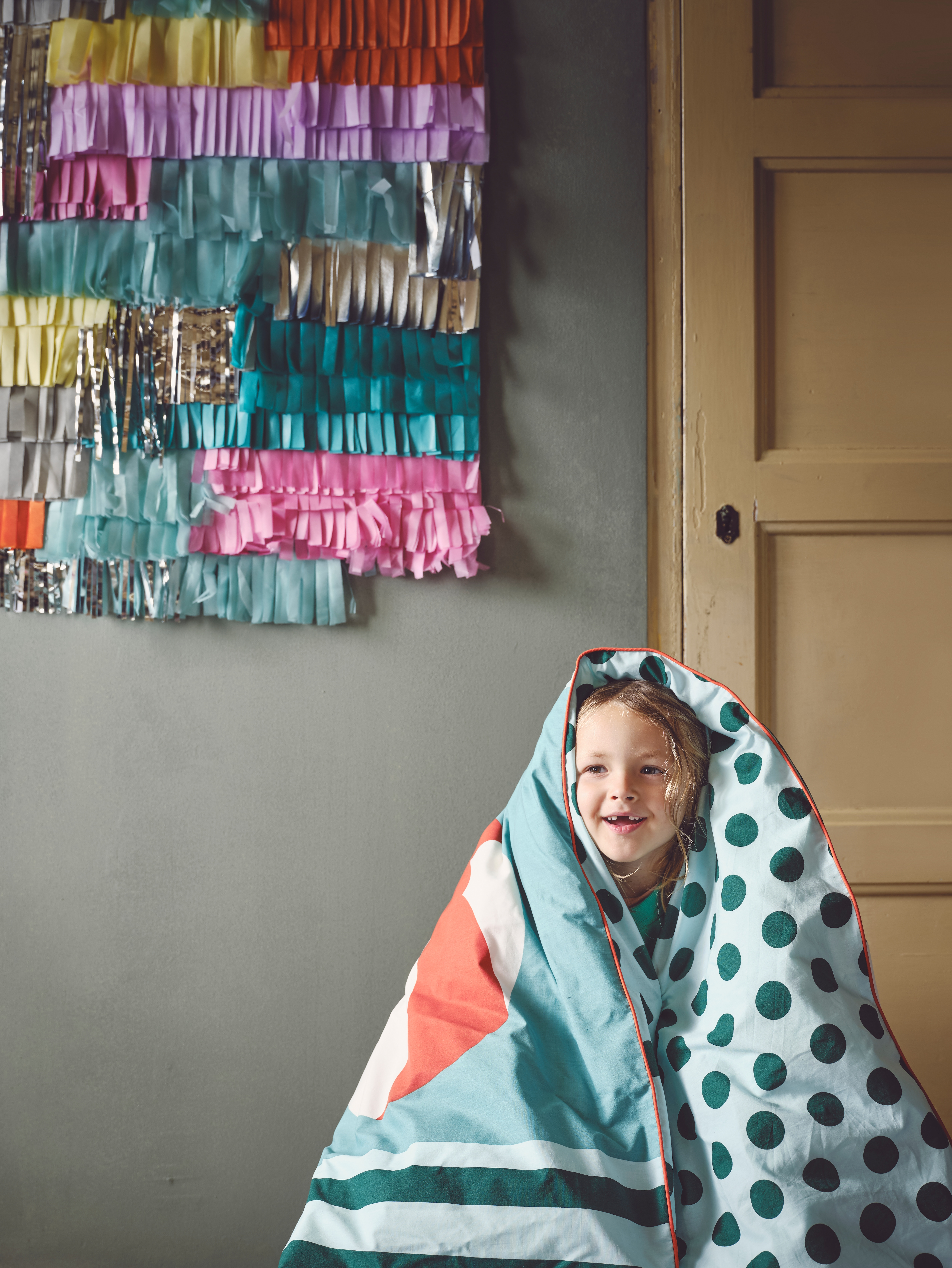 Close-up of child playing with colourful quilt cover, in room with yellow door, grey walls and collourful fringe pattern.