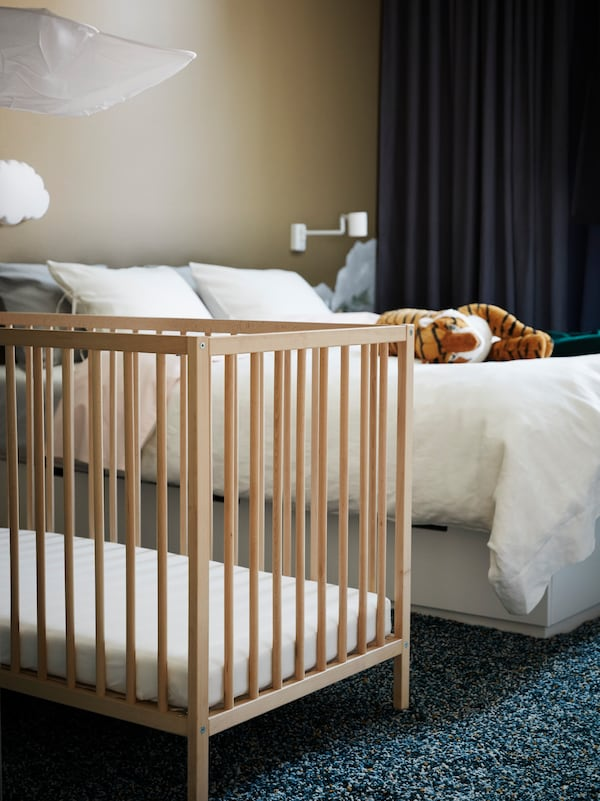 Una cuna SNIGLAR en madera de haya en un dormitorio, cerca de una cama doble sobre la que hay un tigre de peluche DJUNGELSKOG.