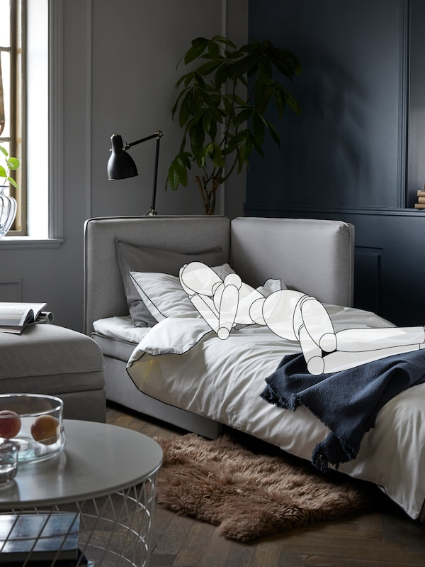 In a living room, a cartoon drawing of a person sleeps on a VALLENTUNA sofa-bed. A lamp and a plant are behind the sofa-bed.