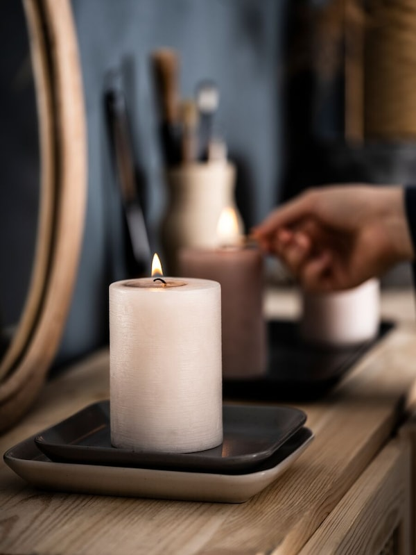 Eine Person hält ein Streichholz in der Hand und zündet Kerzen in Rosa an, die auf eckigen Tellern stehen. Dahinter befindet sich eine Kanne mit Pinseln.