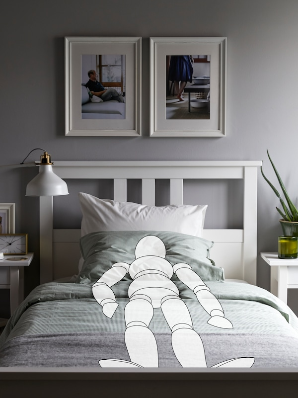 A cartoon drawing of a person lies sleeping on a white HEMNES bed. There are two pictures on the wall above the bed.
