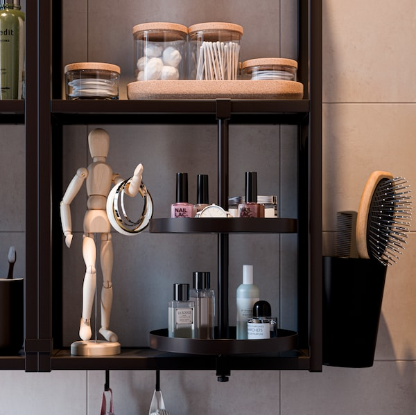 A wall-mounted black ENHET shelving unit and swivel shelf holding glass containers and other bathroom items.