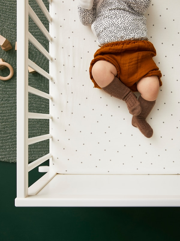 A small child wearing a dotted top, brown shorts and long brown socks lies on its back in a white cot.
