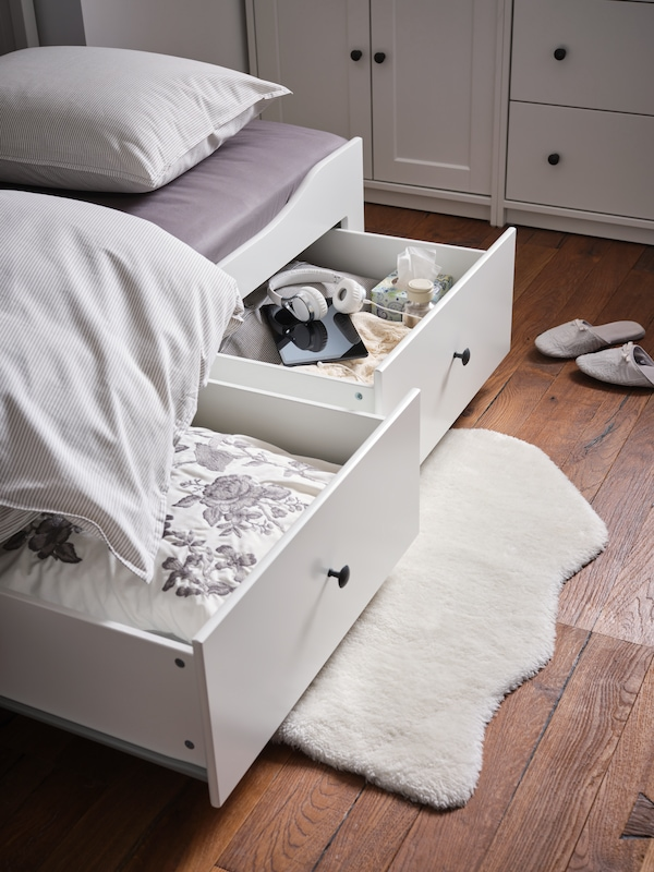 Two HEMNES drawers on a bed pulled out with folded up beddings inside.