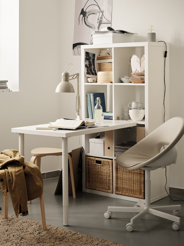 A white KALLAX shelving unit standing against a wall in a white home office with various items and an attached desk.