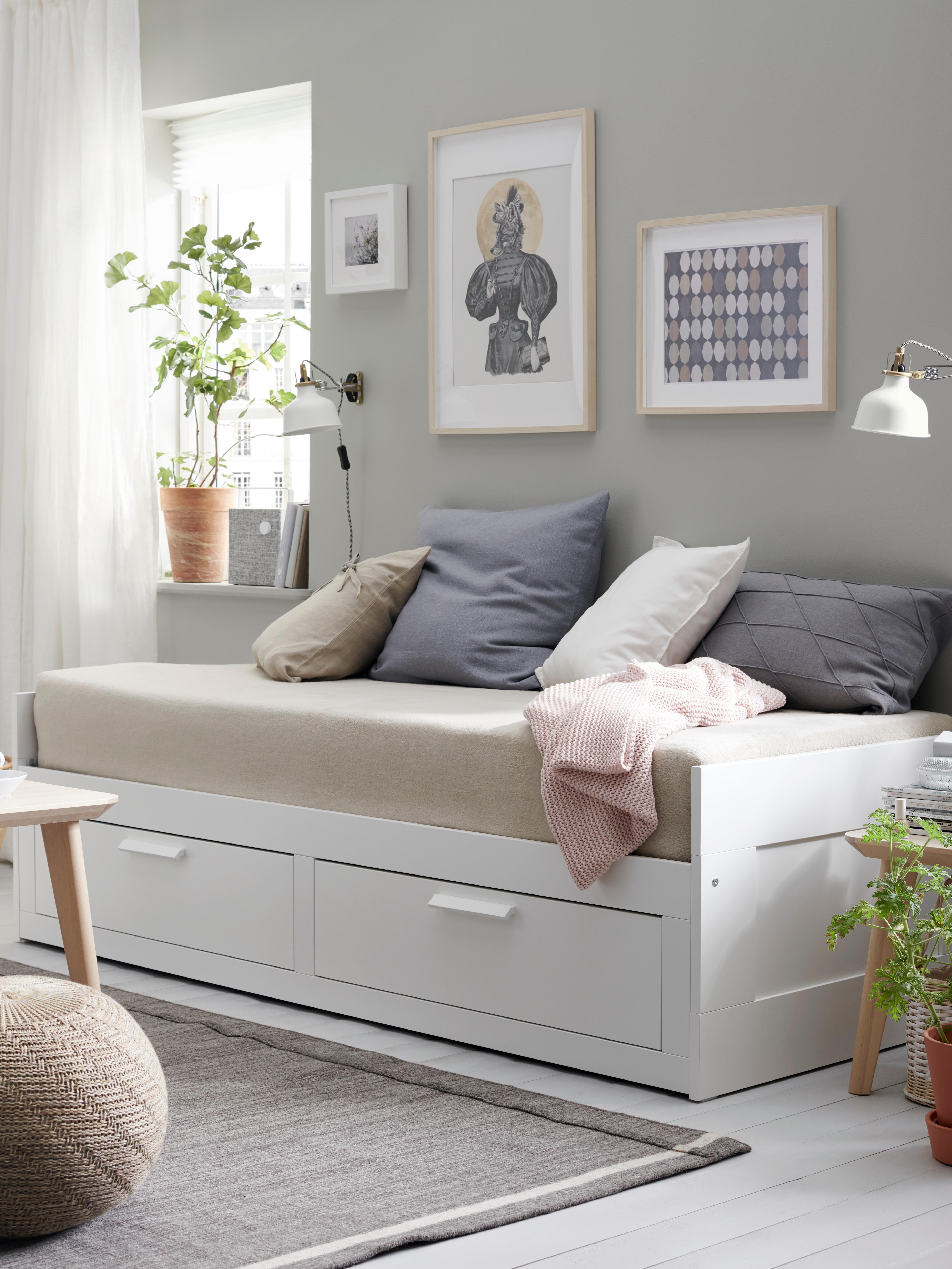 Letto divano BRIMNES bianco con due cassetti, accostato a una parete, con una copertura beige su entrambi i materassi.