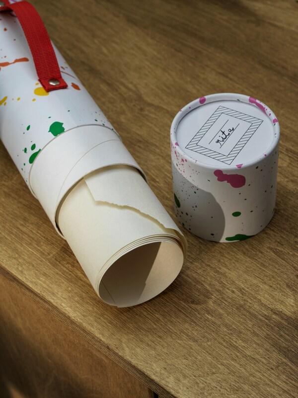 Un tube de transport MÅLA ouvert, contenant une feuille enroulée, se trouve sur une surface en bois. Le couvercle du tube se trouve à côté.