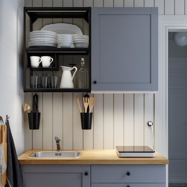 An ENHET kitchen in grey and anthracite against a wall with striped wallpaper. Kitchenware is stacked in an open cupboard.