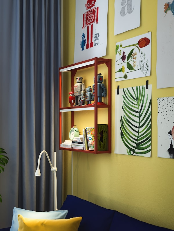 A red ENHET wall frame with shelves on a yellow wall, displaying robot toys, notebooks and a green alarm clock.