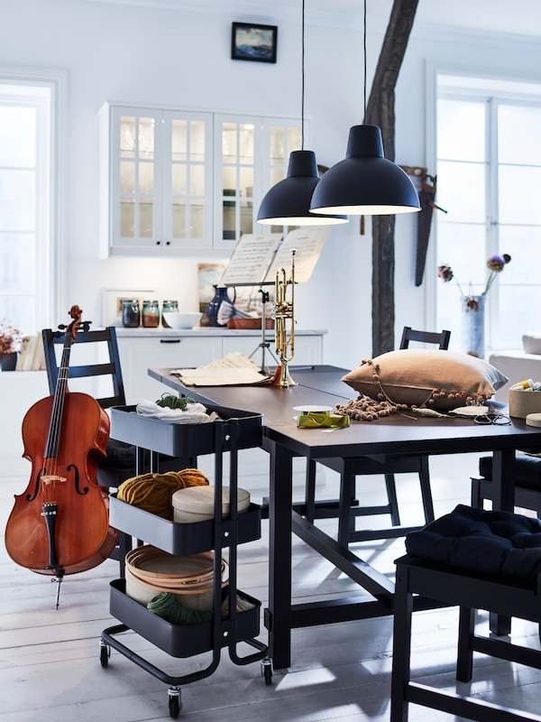 117/5000 Bílá kuchyň s černým rozkládacím stolem a čtyřmi černými židlemi. Hudební nástroje jsou na stole i kolem něj.