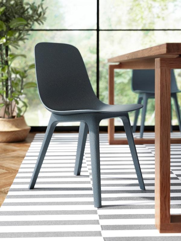 Sedia ODGER blu su tappeto bianco e nero, accanto a un tavolo MÖRBYLÅNGA in impiallacciatura di rovere con mordente marrone.