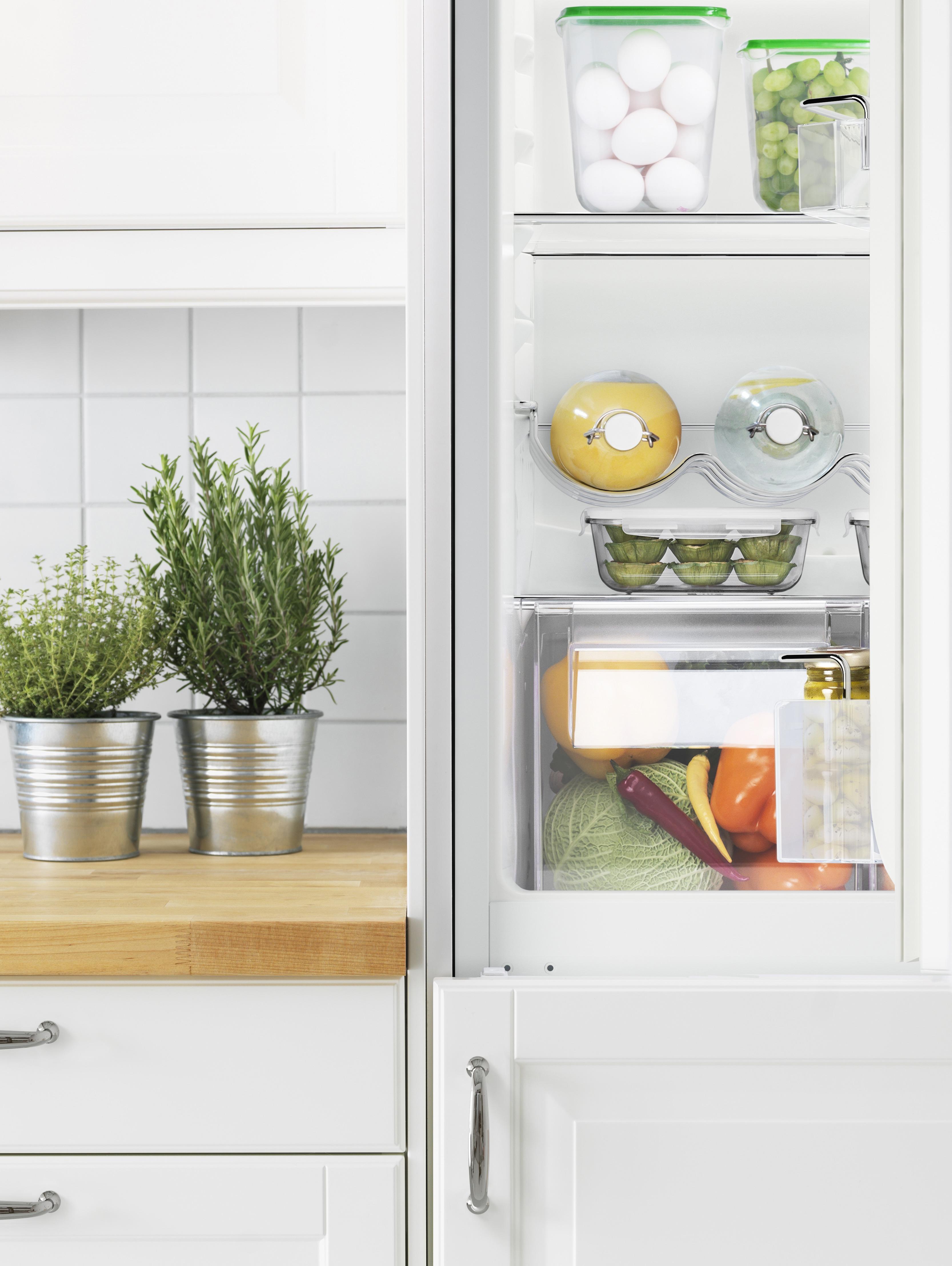 Un réfrigérateur / congélateur ISANDE ouvert révélant des étagères soigneusement empilées.