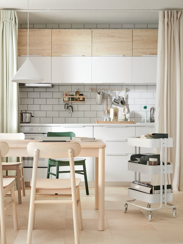 A table and coloured chairs beside a RÅSKOG trolley in front of a curtain-framed kitchen fitted with white VEDDINGE doors.