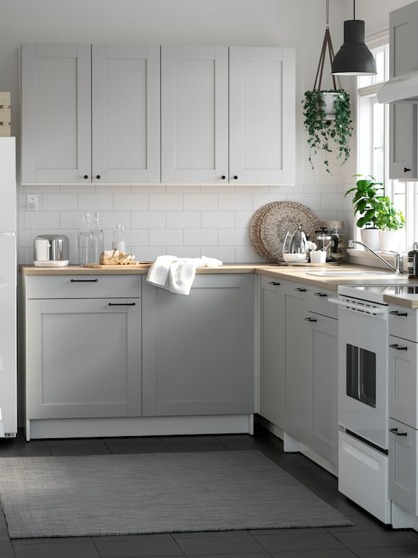 A grey KNOXHULT kitchen with cabinets with bevelled edges and black knobs and handles. A plant hangs in the corner.