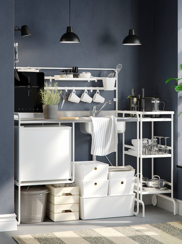 A white SUNNERSTA mini-kitchen with two pendant lamps against a blue-grey wall, and white storage boxes underneath.