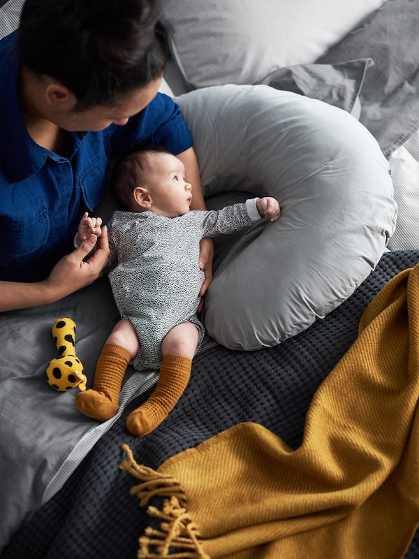 A woman sits on a bed resting her arm on a LEN nursing pillow and holding a baby. A yellow OMTÄNKSAM throw lies nearby.