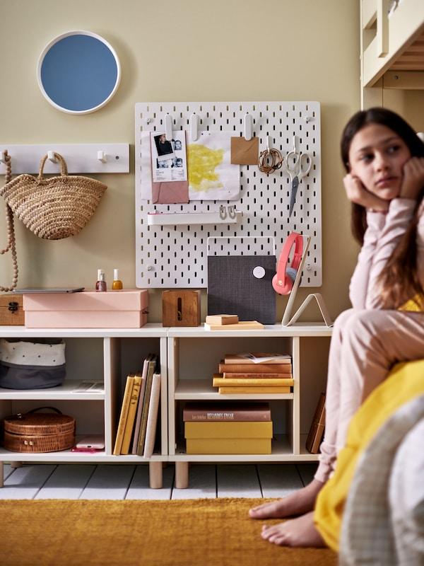 فتاة تجلس على حافة الطابق السفلي من سرير بطابقين بجانب وحدتي تخزين SMUSSLA منخفضتين باللون الأبيض أعلاهما لوح تعليق أبيض.