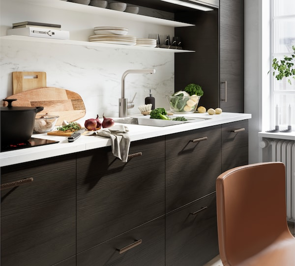 A kitchen with ASKERSUND drawers in dark brown and red onions, broccoli and cauliflower on a KASKER worktop in marble design.
