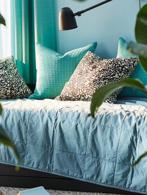 Different cushions lie on a day-bed which is covered with a green GULVED bedspread. A SKURUP lamp is on the wall nearby.