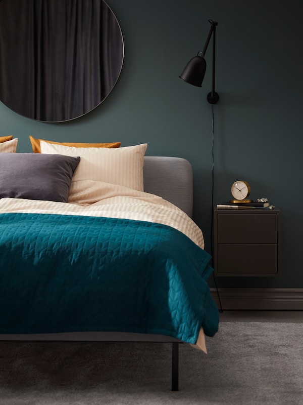 A bedroom with a rich turquoise blanket.