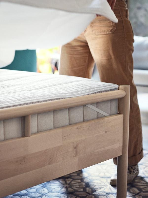 BJÖRKSNÄS 비에르크스네스 침대 위 VATNESTRÖM 바트네스트룀 매트리스에 깔린 ROSENVIAL 로센비알 매트리스보호패드 위에 화이트 시트를 깔고 있는 여성.