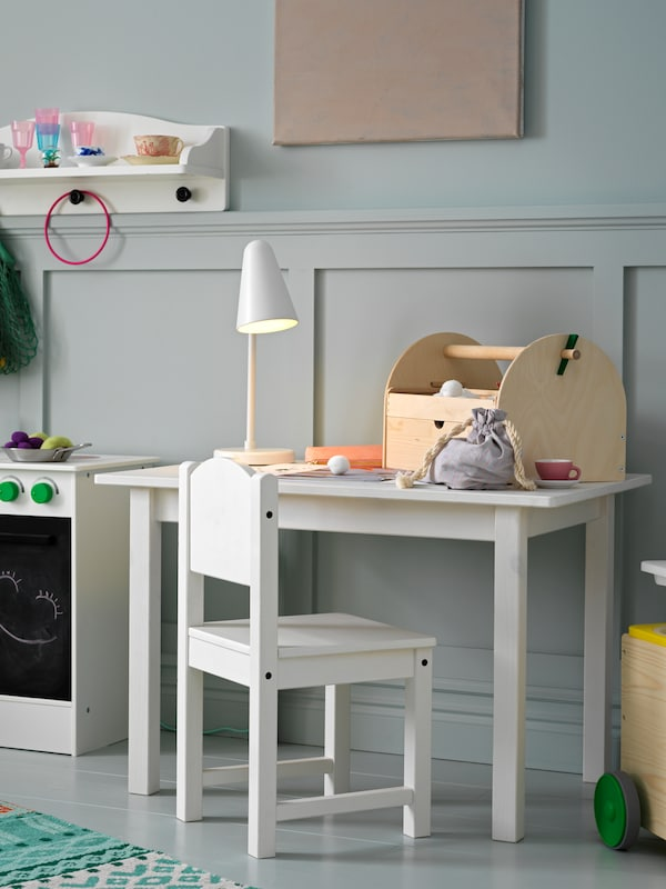 Scaun și masă pentru copii cu veioză și lucrări artizanale deasupra, alături de care se află o bucătărie albă de jucărie.