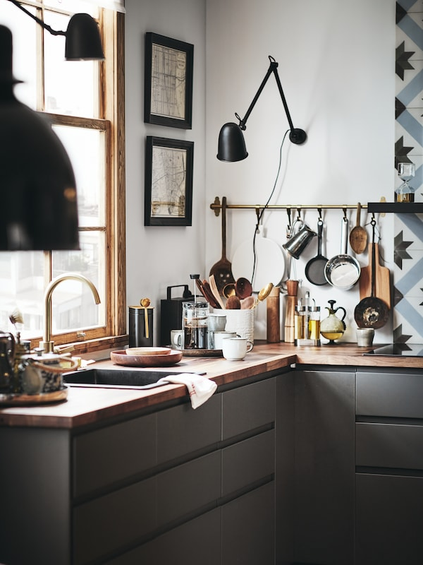 A METOD kitchen with a wooden worktop. On the worktop are kitchen utensils, mugs and a coffee pot, with a rail on the wall.