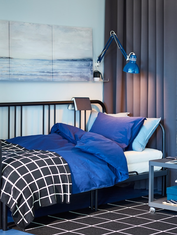 A blue hued bedroom with a black metal daybed and bright blue bedding. A lit lamp shines overhead.