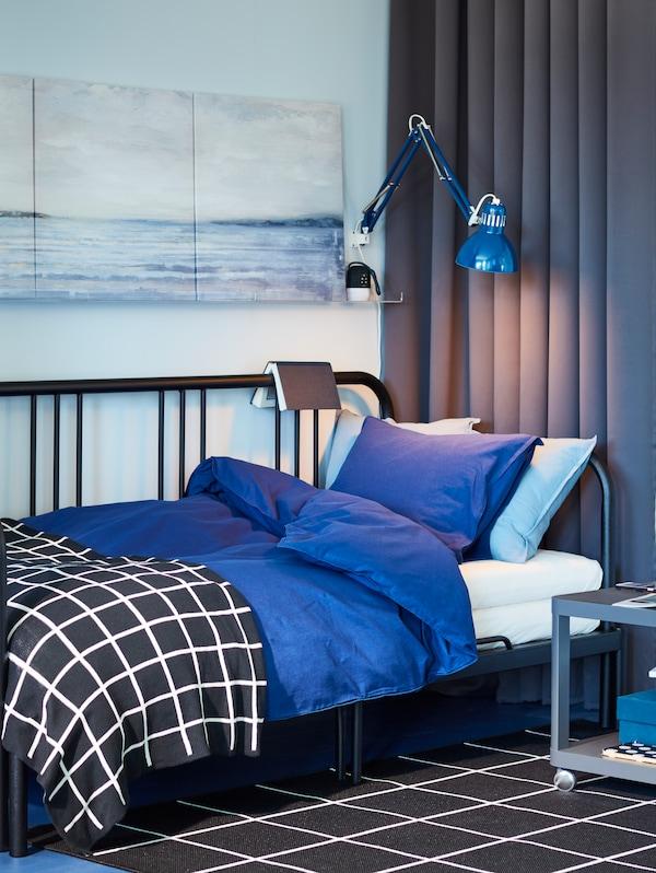 Un pat de zi negru, cu așternuturi de pat albastre, perdele de blocare, un covor alb-negru și o veioză.