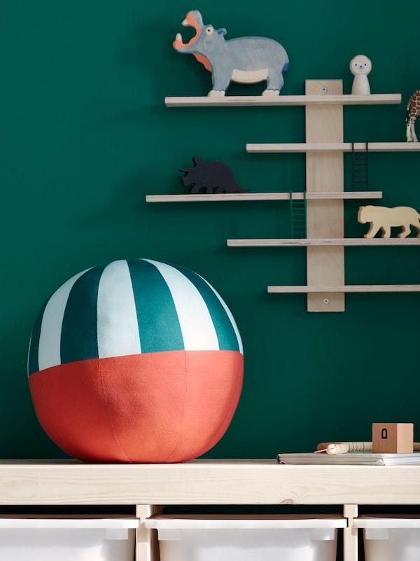 A KÄPPHÄST soft toy, shaped like a ball, sits on top of TROFAST storage near a LUSTIG wall shelf on the wall.