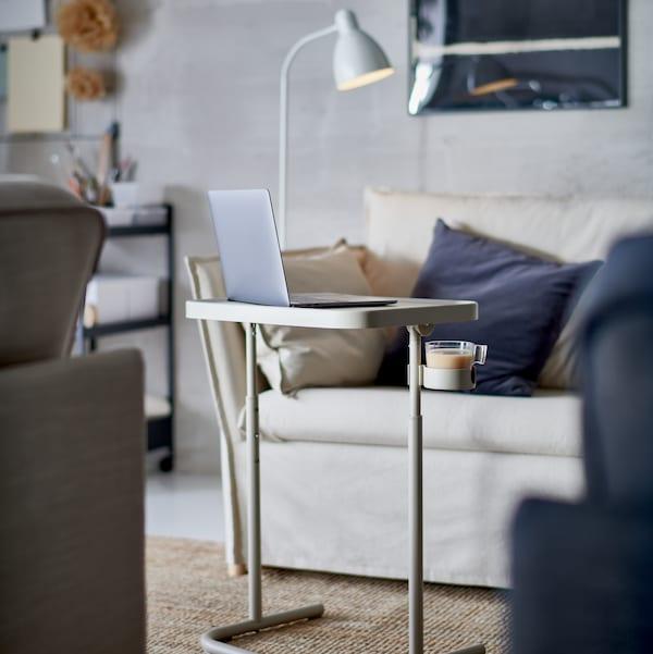 كمبيوتر محمول على حامل كمبيوتر محمول BJÖRKÅSEN أمام كرسي بذراعين 1.5 مقعد لون طبيعي وبعض الوسائد.