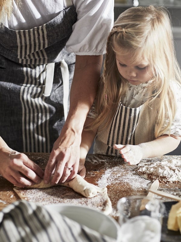 A young girl wearing a beige MARIATHERES apron is standing next to a woman and they are together kneading a dough.