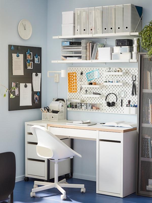 Der MICKE Schreibtisch mit einem LOBERGET / BLYSKÄR Drehstuhl steht vor einer Wand, An der Wand sind Wandregale, eine Uhr, eine Pinwand und Zeitschriftensammler zu sehen.