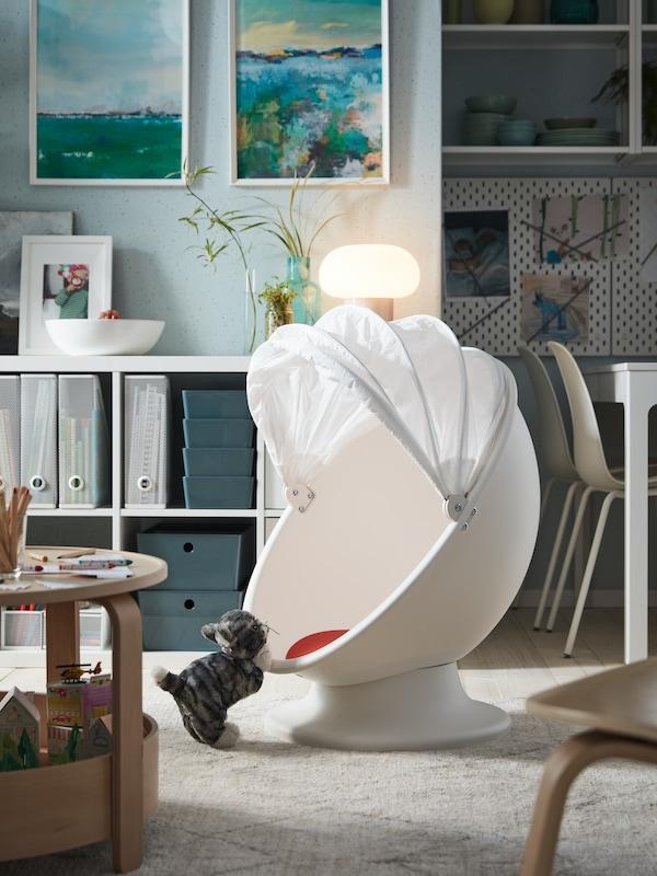 En hvid/rød drejelænestol, en grå/hvid tøjdyrskat, et sofabord med legetøj og malerier på væggen.